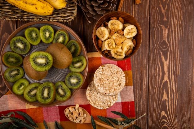 Bovenaanzicht van plakjes kiwi's op een bord en gesneden bananen met amandel in een houten kom, houten lepel met pinda's en rijstcrackers op rustiek met kopie ruimte