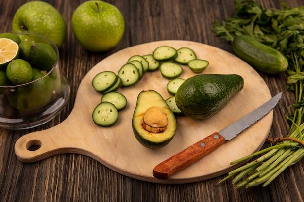 Bovenaanzicht van plakjes komkommer op een houten keukenbord met avocado met mes met feijoas op een glazen kom met groene appels en peterselie geïsoleerd op een houten oppervlak