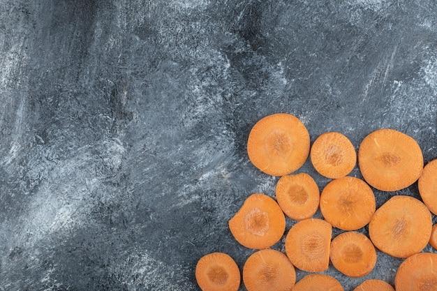 Bovenaanzicht van plakjes wortel op grijze achtergrond.