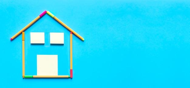 Bovenaanzicht van plaknotities en fluorescerende markeerstiften die een tekening vormen van een huis op een pastelblauwe achtergrond.