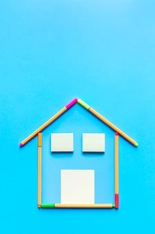 Bovenaanzicht van plaknotities en fluorescerende markeerstiften die een tekening vormen van een huis op pastelblauwe achtergrond.
