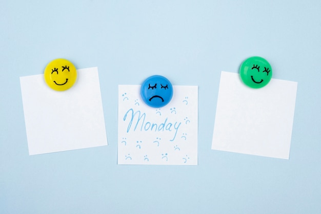 Bovenaanzicht van plaknotities met droevig gezicht voor blauwe maandag en smileygezichten