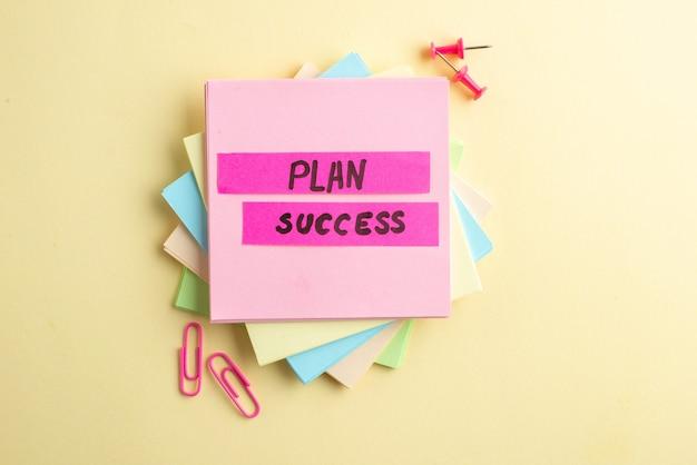 Bovenaanzicht van plan succes schrijven op gestapelde notitieblokjes en paperclips punaises op gearceerde gele achtergrond met vrije ruimte