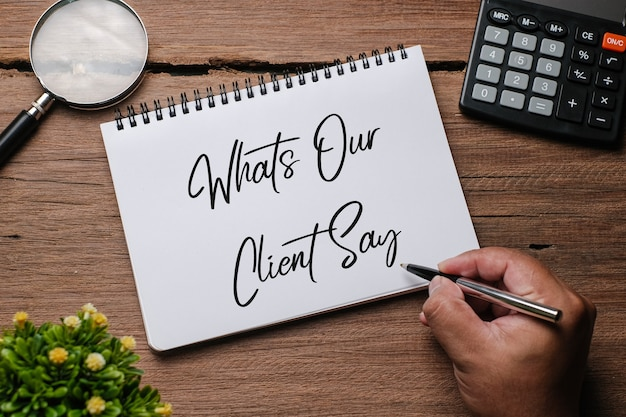 Bovenaanzicht van plant, bril, klok en hand met pen schrijven 'wat onze klanten zeggen' op notitieboek over houten achtergrond.