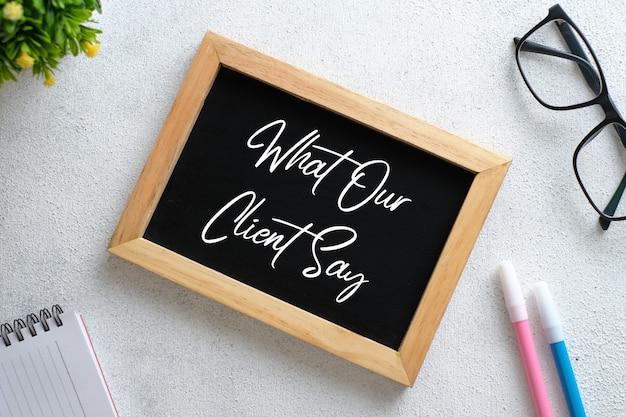 Bovenaanzicht van plant, bril, klok en hand met pen schrijven 'wat onze klanten zeggen' op schoolbord over houten achtergrond.