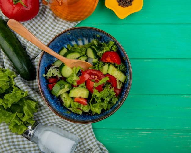 Bovenaanzicht van plantaardige salade met tomatensla komkommer zout en zwarte peper op doek en groene oppervlak met kopie ruimte
