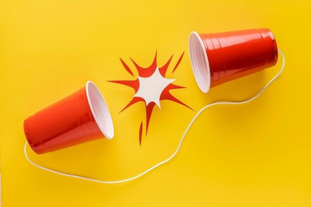 Bovenaanzicht van plastic bekers bevestigd met touwtje en papiervorm