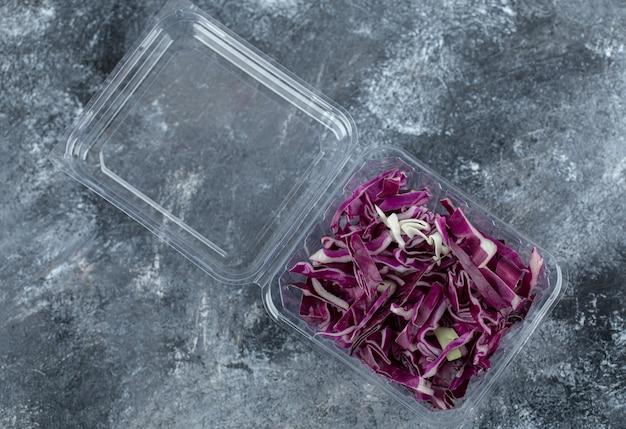 Bovenaanzicht van plastic container vol met gehakte paarse kool over grijze achtergrond.