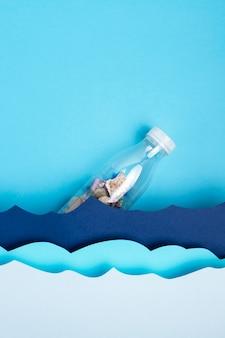 Bovenaanzicht van plastic fles met papier oceaangolven