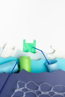 Bovenaanzicht van plastic zakken en rietjes in papier oceaan