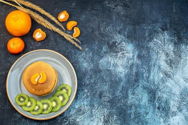 Bovenaanzicht van pluizige amerikaanse pannenkoeken gemaakt met natuurlijke yoghurt geserveerd met kiwi's en mandarijn op een bord en fruit spikes op ijs achtergrond met vrije ruimte