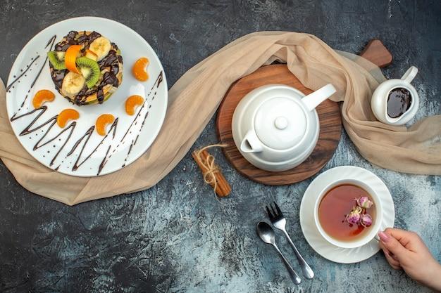 Bovenaanzicht van pluizige pannenkoeken in amerikaanse stijl gemaakt met natuurlijke yoghurt en gestapeld met lagen fruit versierd met chocolade op witte plaat theeset op ijsachtergrond