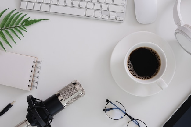 Bovenaanzicht van podcastmicrofoon, plant, toetsenbord, koffiekopje, bril en witte achtergrond