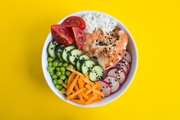 Bovenaanzicht van poke bowl met rode garnalen en groenten