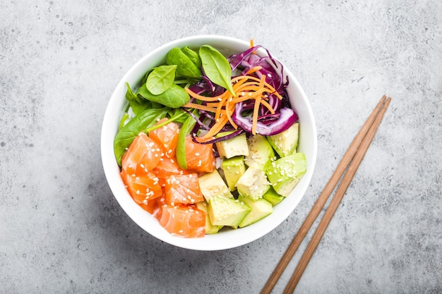 Bovenaanzicht van poke bowl met verse rauwe zalm, avocado, rijst, spinazie, groenten. traditionele hawaiiaanse schotel op rustieke stenen achtergrond. gezond en schoon eten concept. poke met plakjes rauwe vis