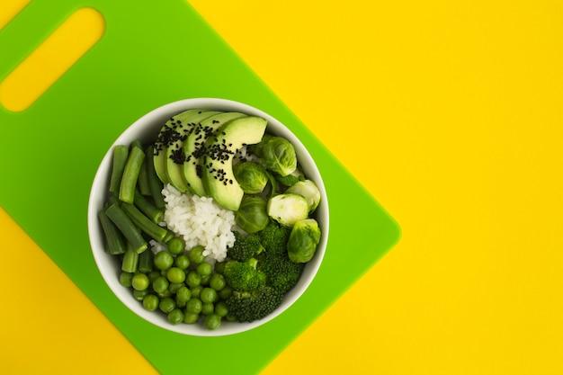 Bovenaanzicht van poke bowl met witte rijst en groene groenten