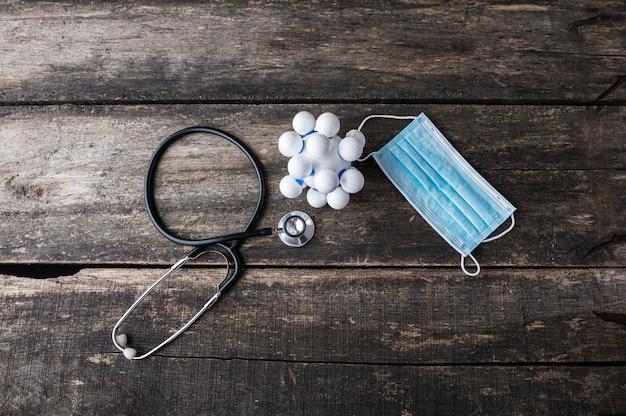 Bovenaanzicht van polystyreen gemaakt figuur van coronavirus molecuul naast een stethoscoop en medisch beschermend masker.