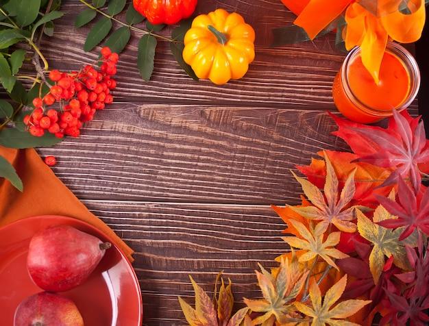 Bovenaanzicht van pompoen met herfstbladeren en kaars