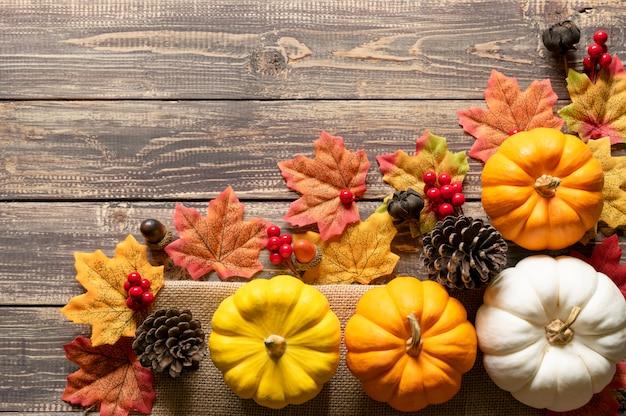 Bovenaanzicht van pompoen, rode bessen, dennenappels en herfstbladeren