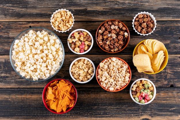 Bovenaanzicht van popcorn en chips in kommen op donkere houten horizontaal