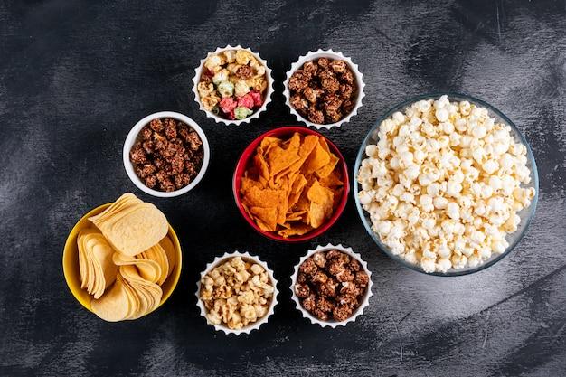 Bovenaanzicht van popcorn en chips in kommen op zwarte horizontaal