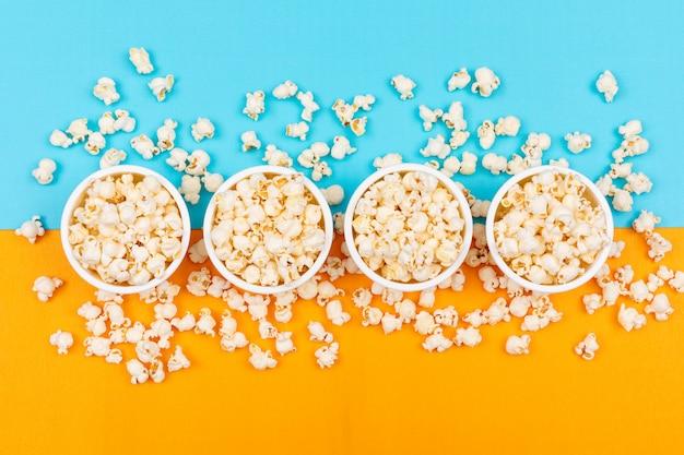 Bovenaanzicht van popcorn in kommen op blauwe en gele horizontaal