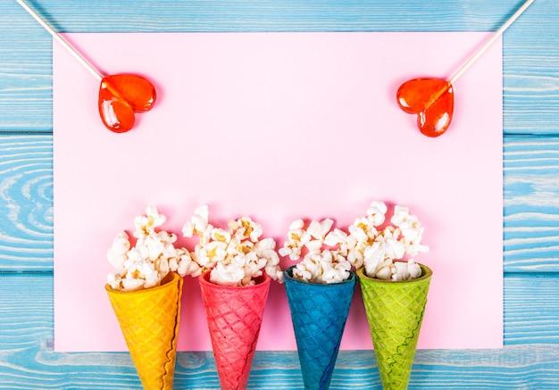 Bovenaanzicht van popcorn met karamel in wafel kegels en lollies