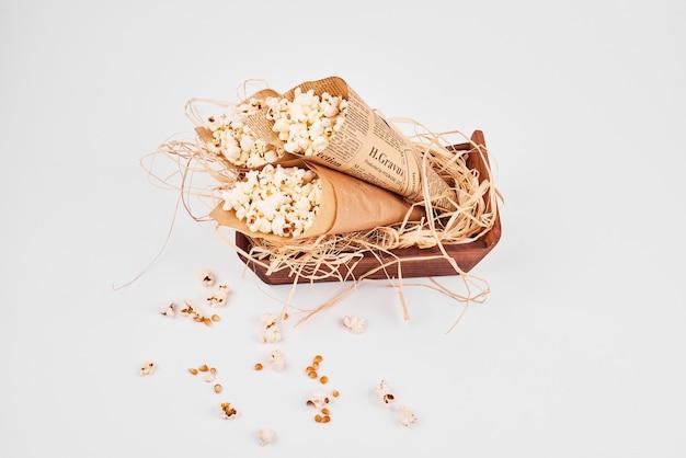 Bovenaanzicht van popcorn verpakt in papier op wit geïsoleerd.
