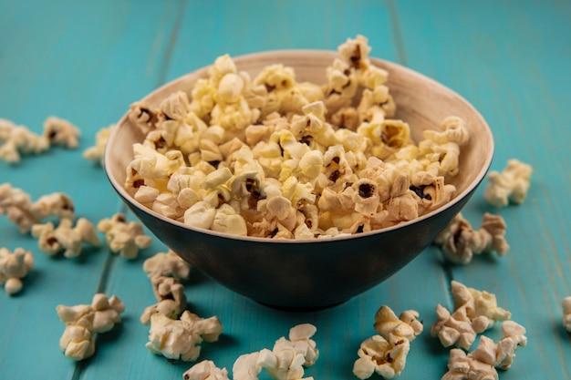 Bovenaanzicht van popcorns op een kom met popcorns geïsoleerd op een blauwe houten tafel