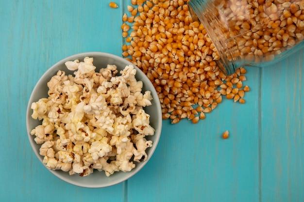 Bovenaanzicht van popcorns pitten vallen uit een glazen pot met lekkere popcorns op een kom op een blauwe houten tafel