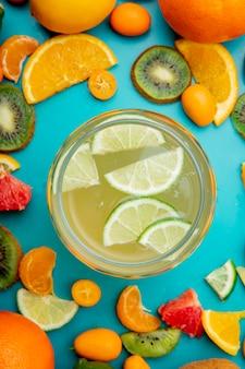 Bovenaanzicht van pot citroensap en citrusvruchten rond op blauw oppervlak