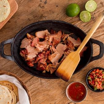 Bovenaanzicht van pot met arepasvulling en saus