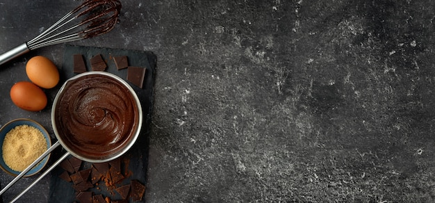 Bovenaanzicht van pot met warme chocolademelk op donkere achtergrond