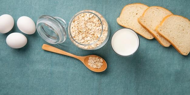 Bovenaanzicht van pot vol havervlokken met eieren melk witbrood plakjes en houten lepel op blauwe achtergrond met kopie ruimte