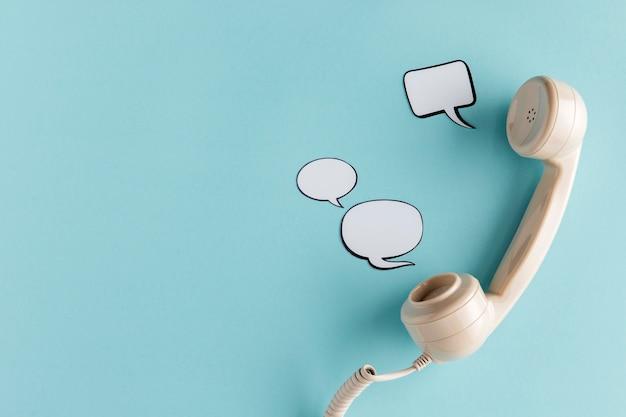Bovenaanzicht van praatjebellen met telefoonhoorn en kopieer de ruimte