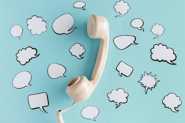 Bovenaanzicht van praatjebellen met telefoonhoorn