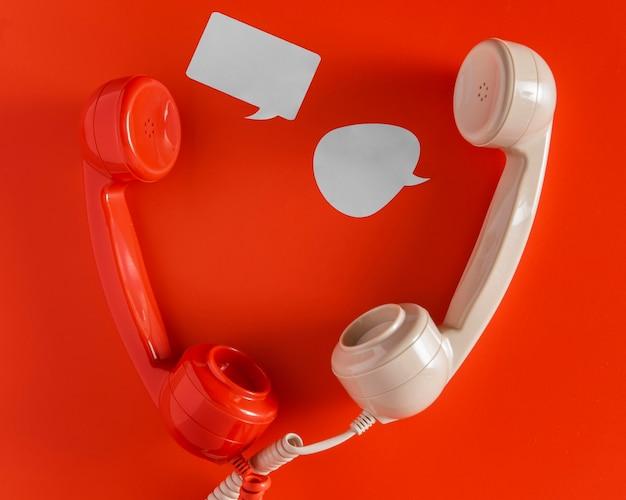 Bovenaanzicht van praatjebellen met twee telefoonontvangers en snoer