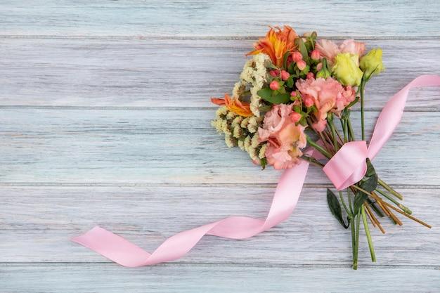 Bovenaanzicht van prachtig boeket bloemen met een roze lint op grijze houten oppervlak