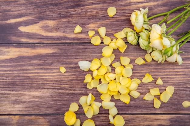 Bovenaanzicht van prachtige en verse pioenrozen met gele bloemblaadjes op een houten oppervlak
