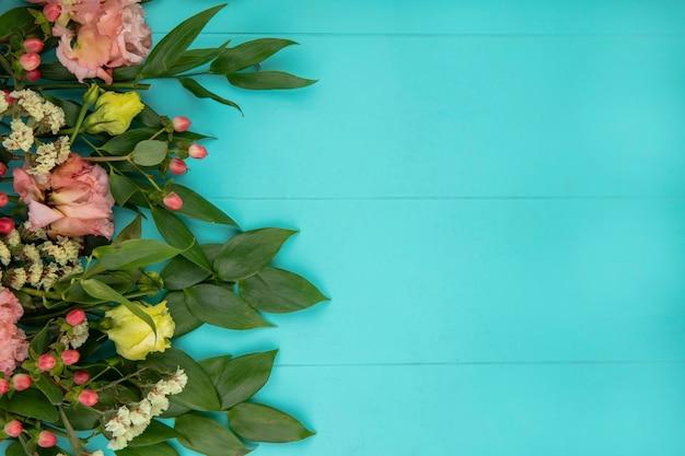 Bovenaanzicht van prachtige gekleurde bloemen met bladeren op blauw met kopie ruimte