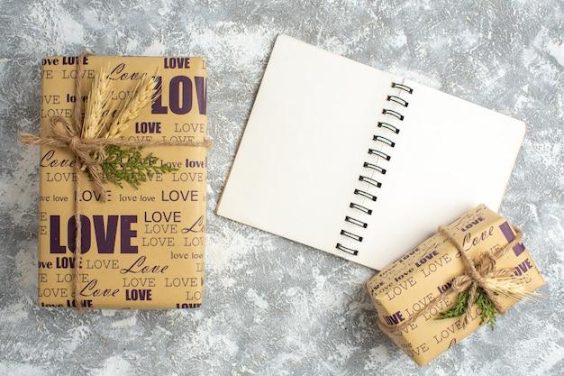 Bovenaanzicht van prachtige kerstcadeaus met liefdesinscriptie op open notitieboekje op ijstafel