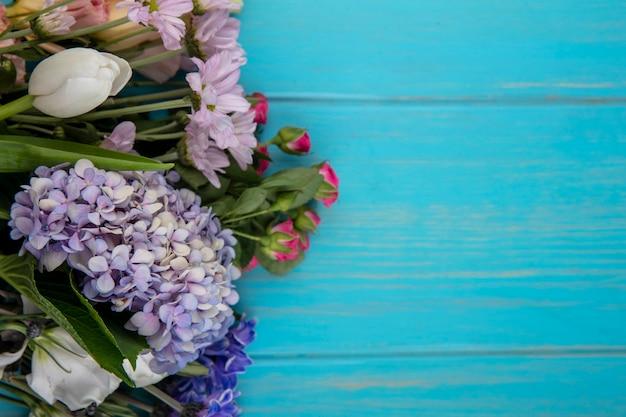 Bovenaanzicht van prachtige kleurrijke bloemen zoals gardenzia rose tulp met bladeren op een blauwe achtergrond met kopie ruimte
