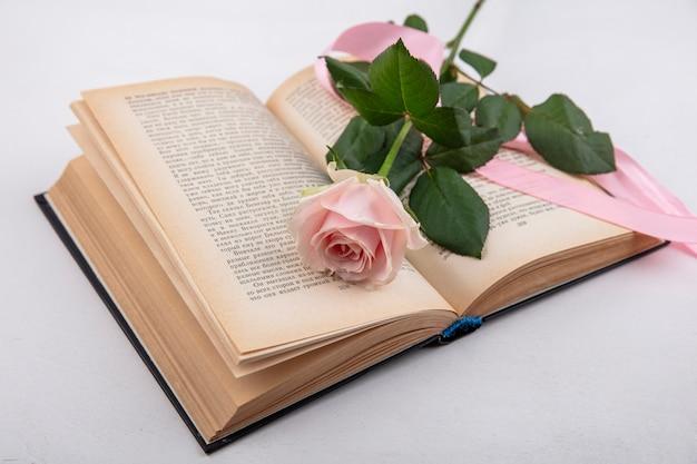 Bovenaanzicht van prachtige roze roos met bladeren over een boek op een witte pagina