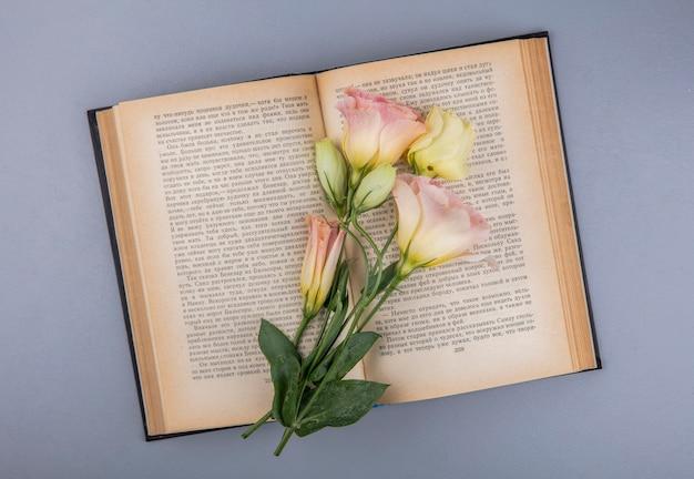 Bovenaanzicht van prachtige verse bloemen over een boek op een grijze achtergrond