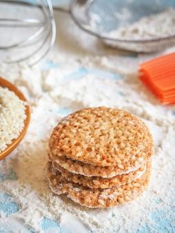 Bovenaanzicht van productset voor het koken van koekjes, keukengerei en verschillende ronde koekjes met sesam.