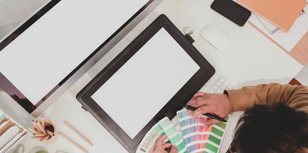Bovenaanzicht van professionele grafisch ontwerper die werkt met kleurstalen
