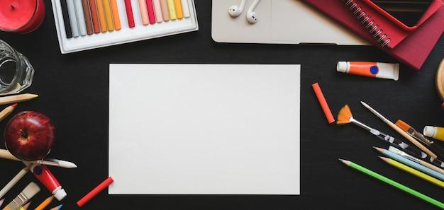 Bovenaanzicht van professionele kunstenaar werkplek met schets papier en tekengereedschappen