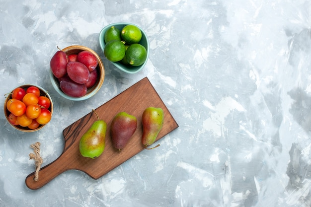 Bovenaanzicht van pruimen en citroenen met peren op lichte witte ondergrond
