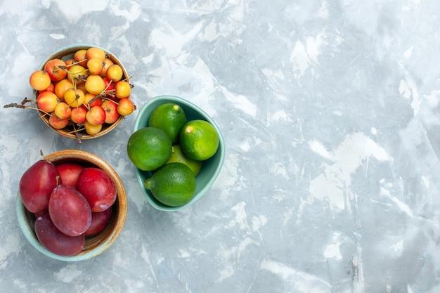 Bovenaanzicht van pruimen en citroenen met zoete kersen op lichte witte ondergrond
