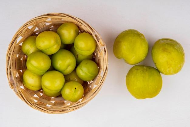 Bovenaanzicht van pruimen in de mand en groene plukken op witte achtergrond